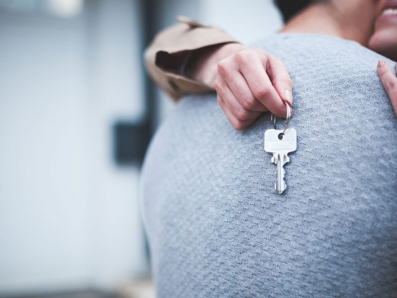 Young woman holding keys hugging husband in front of their new home after buying real estate